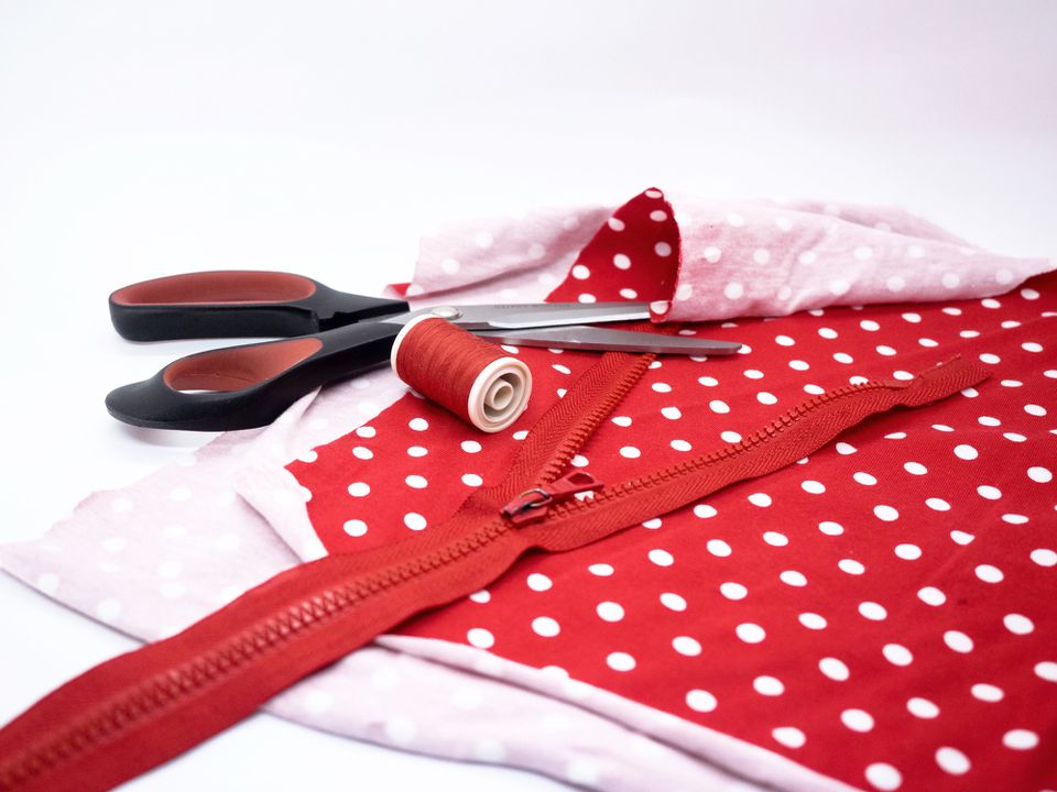 Red fabric, zipper, scissors, and thread used for sewing