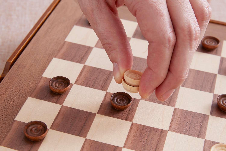 a king checker piece jumping another checker piece