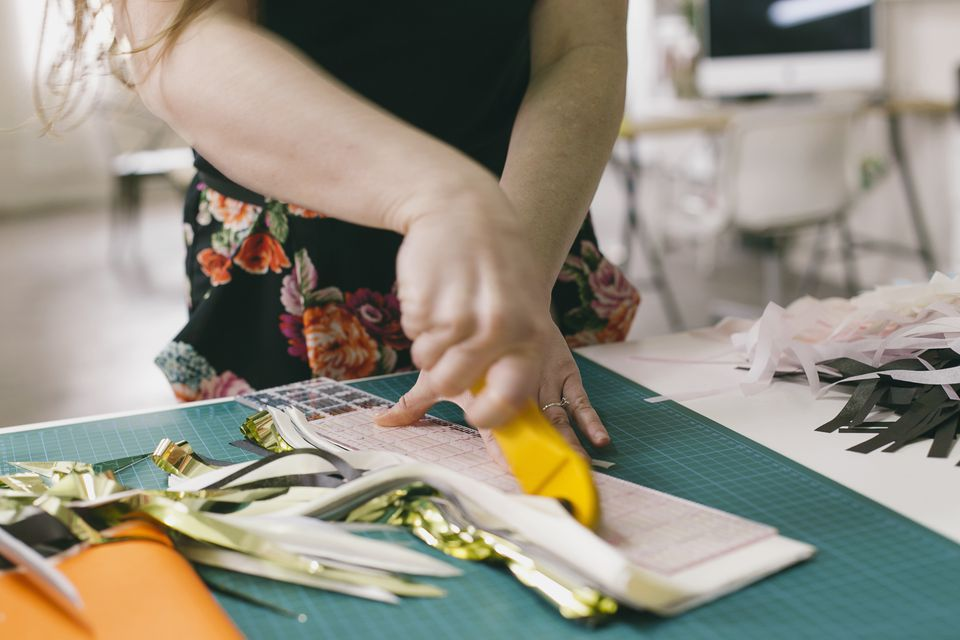 Close up of female textile designer cutting textiles in design studio