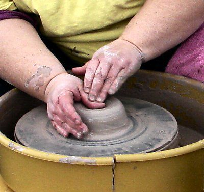 Opening the centered clay on a pottery wheel