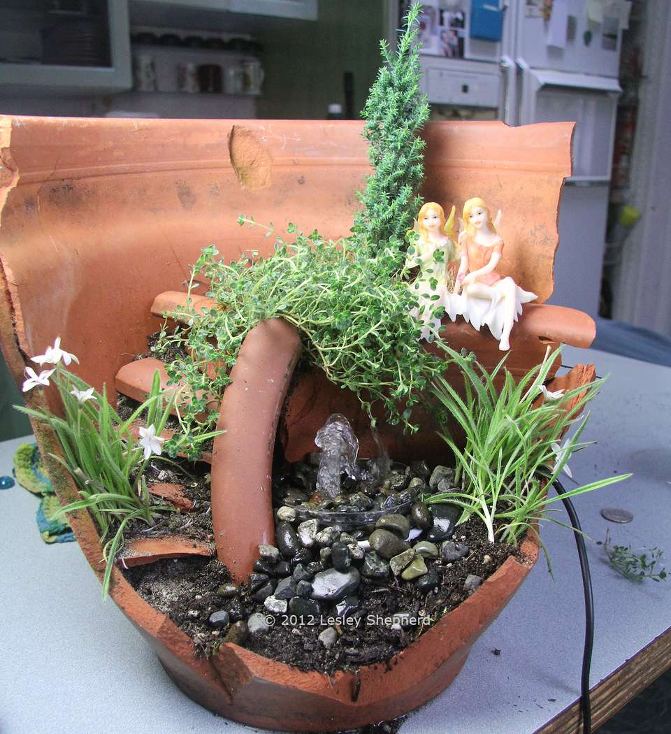 Simple recycling fountain in a miniature garden setting.