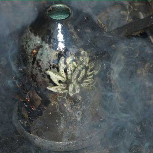 A raku pot wreathed in smoke as it comes out of the combustion chamber.