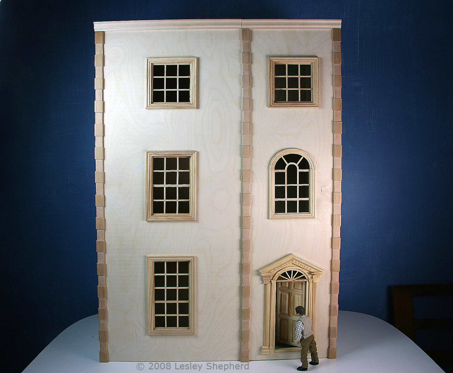 Simple front opening dollhouse finished with strip quoins and cornice trim.