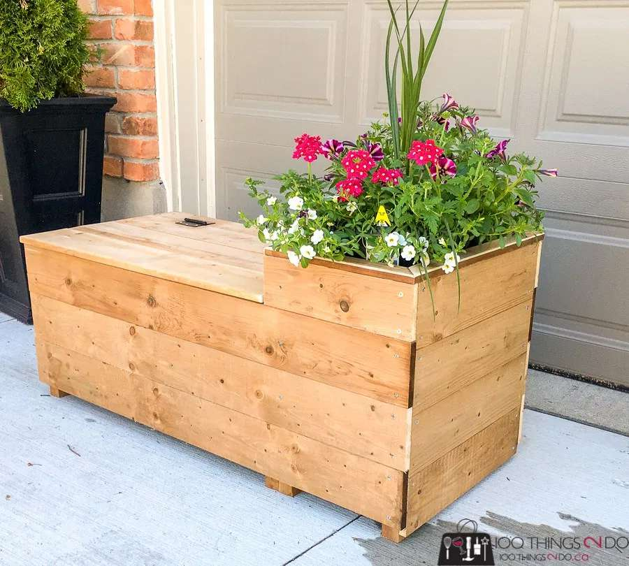 A wooden planter and bench outside of a garage