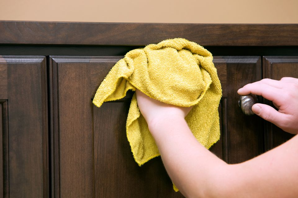 Housecleaner Wiping Dark Stained Cabinet