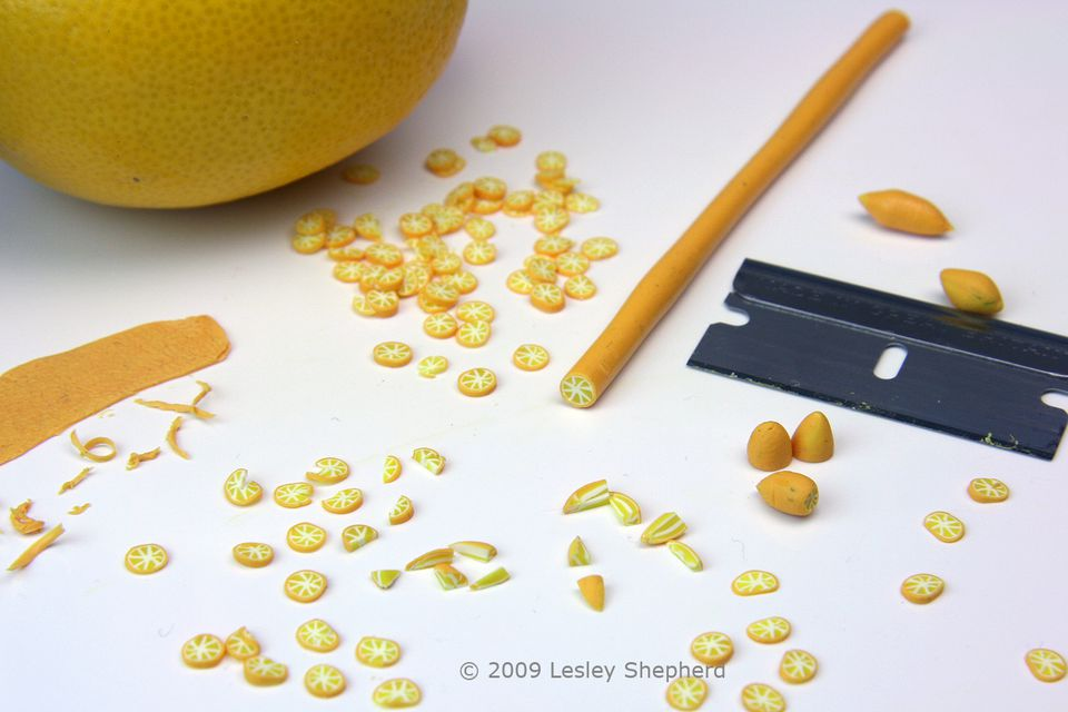 Segments, slices, peel and whole lemons made from polymer clay in dollshouse scale.