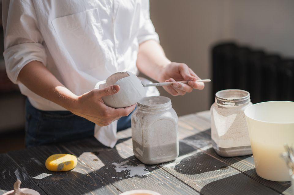 Female potter glazing raw unburned ceramic cup using brush. Earthenware mug putting colorant on pottery workshop