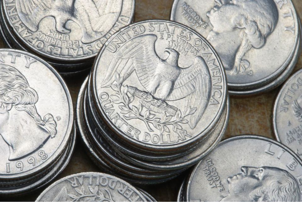 US Currency: Stacked quarter dollar coins, close-up