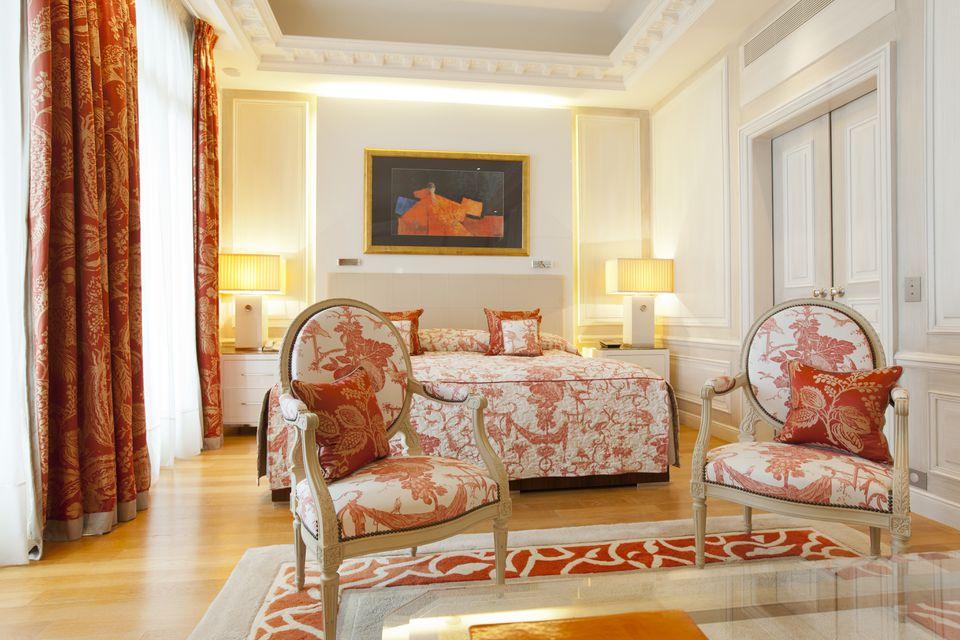 Gorgeous orange and white bedroom with orange drapes.
