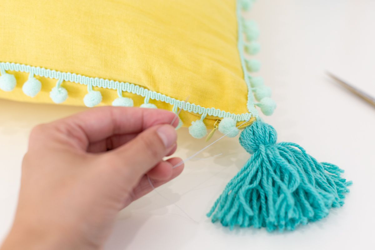 Sewing tassels on a pillow