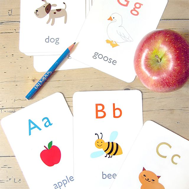 Alphabet Flash Cards Laying on a Table With an Apple and Pencil