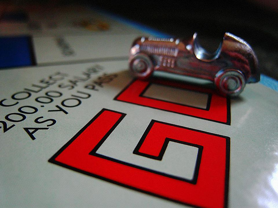 Monopoly board focusing on the Go square with car piece.