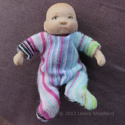 35aefe57a Test fitting a knitted fabric sleeper on a miniature baby doll.