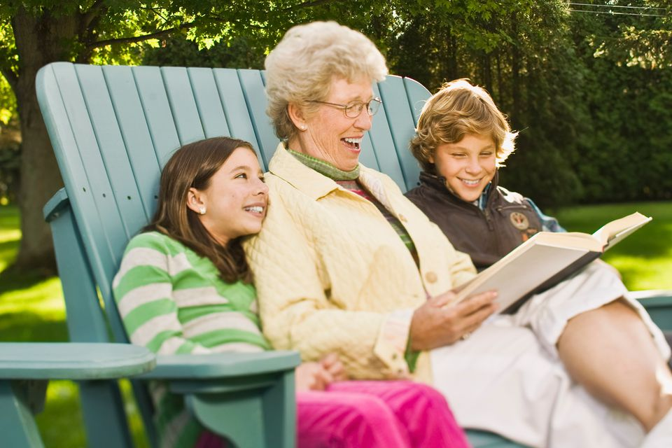 Grandmother reading to grandchildren on adirondack chair
