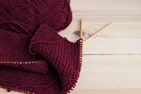 Woolen burgundy yarn knitting on wooden table