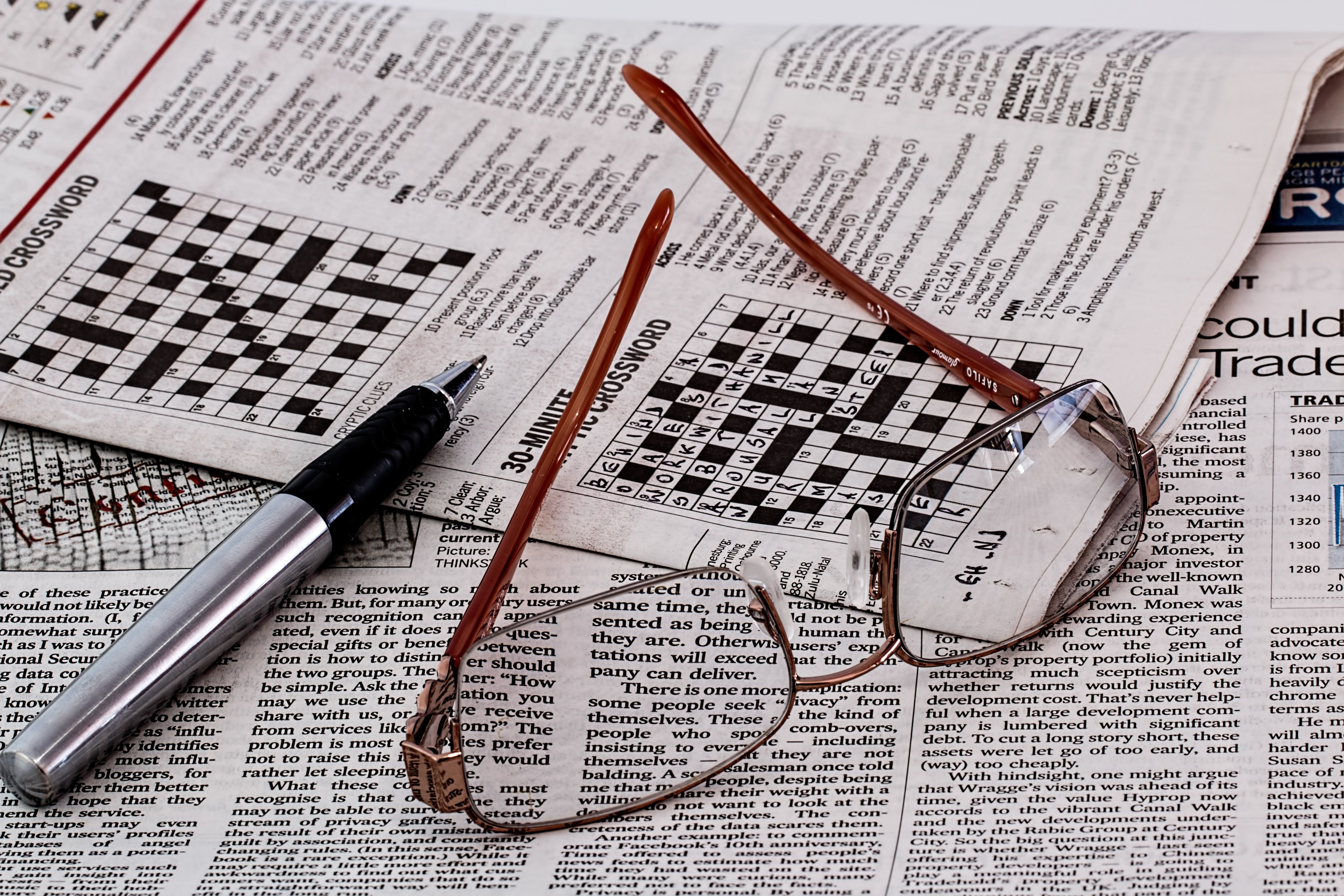 Newspaper crossword and spectacles