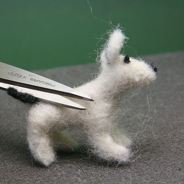 Scissors trim loose fibers from the body of a dolls house scale felted dog.