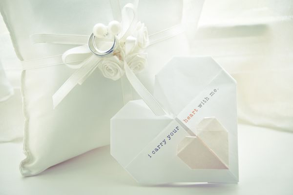 Origami heart decoration next to pillow with wedding rings