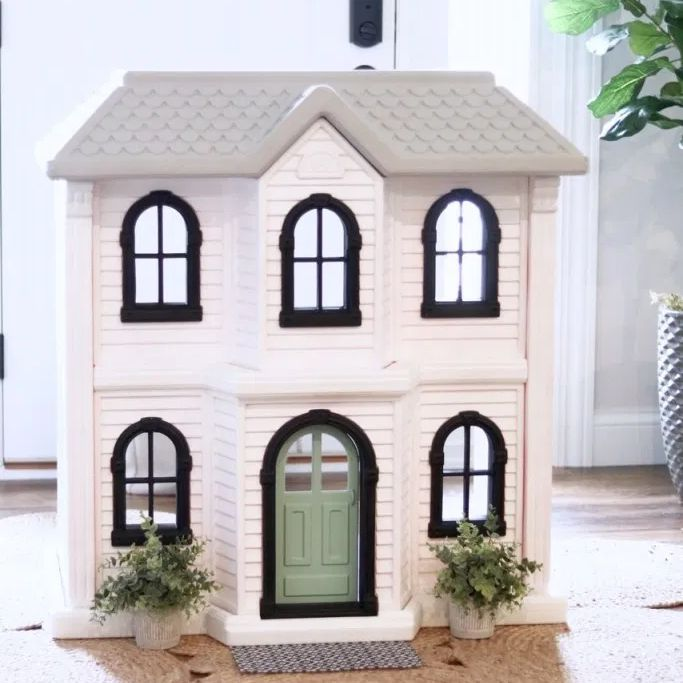 A white dollhouse by a front door