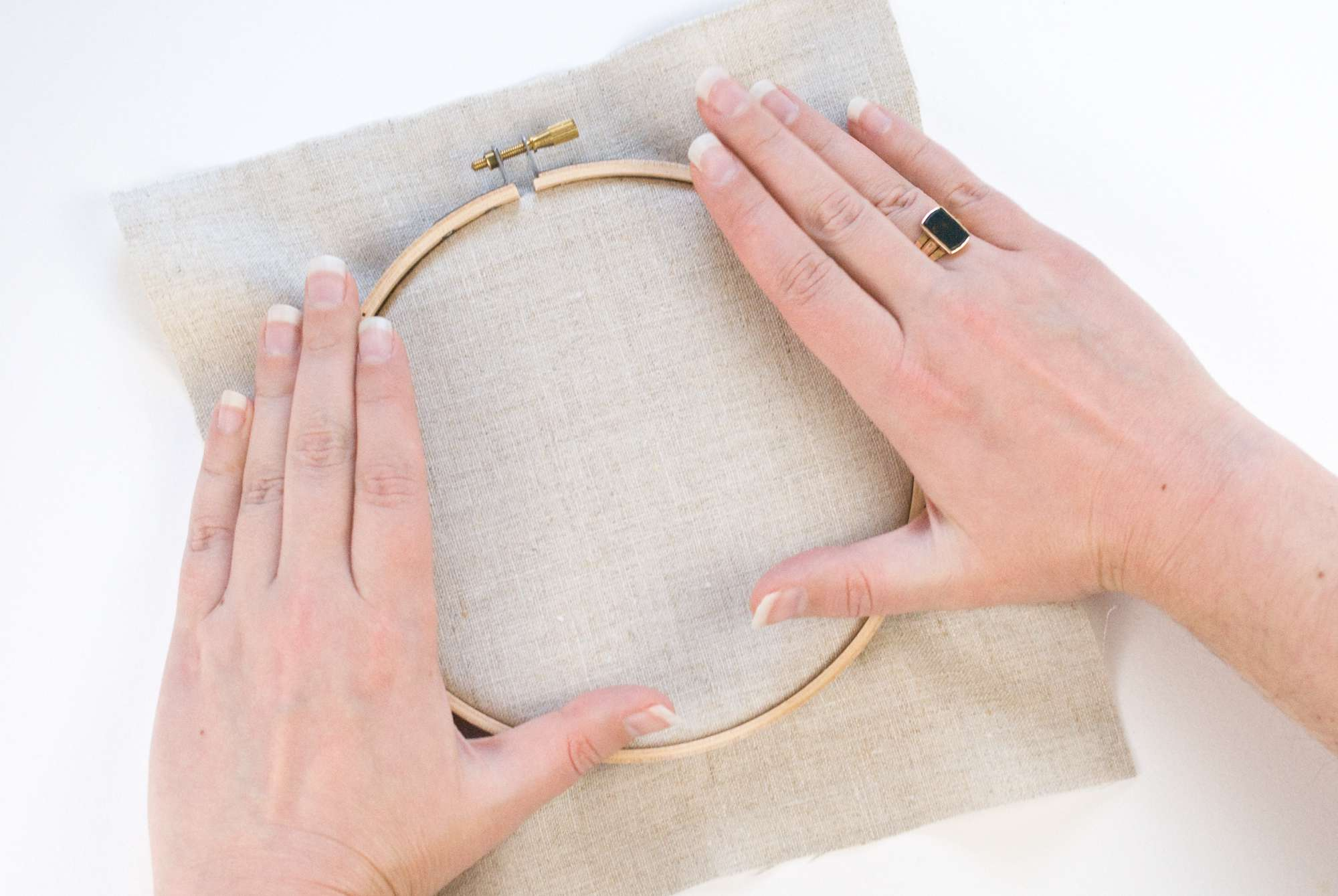 Woman's hand pressing the embroidery hoop over the fabric.