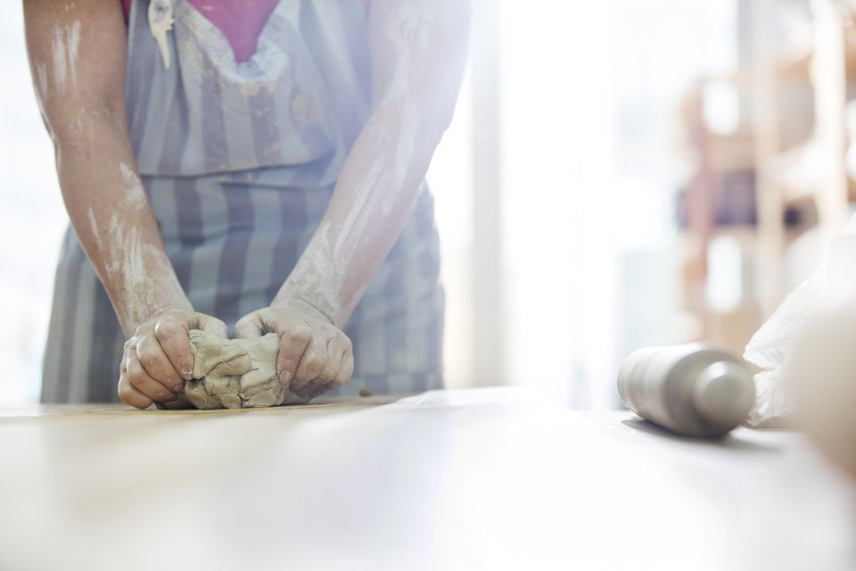 Woman molding pottery clay on a table.