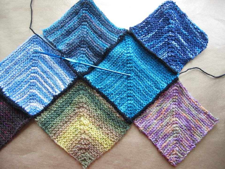 Eight crocheted squares along with a crochet hook.