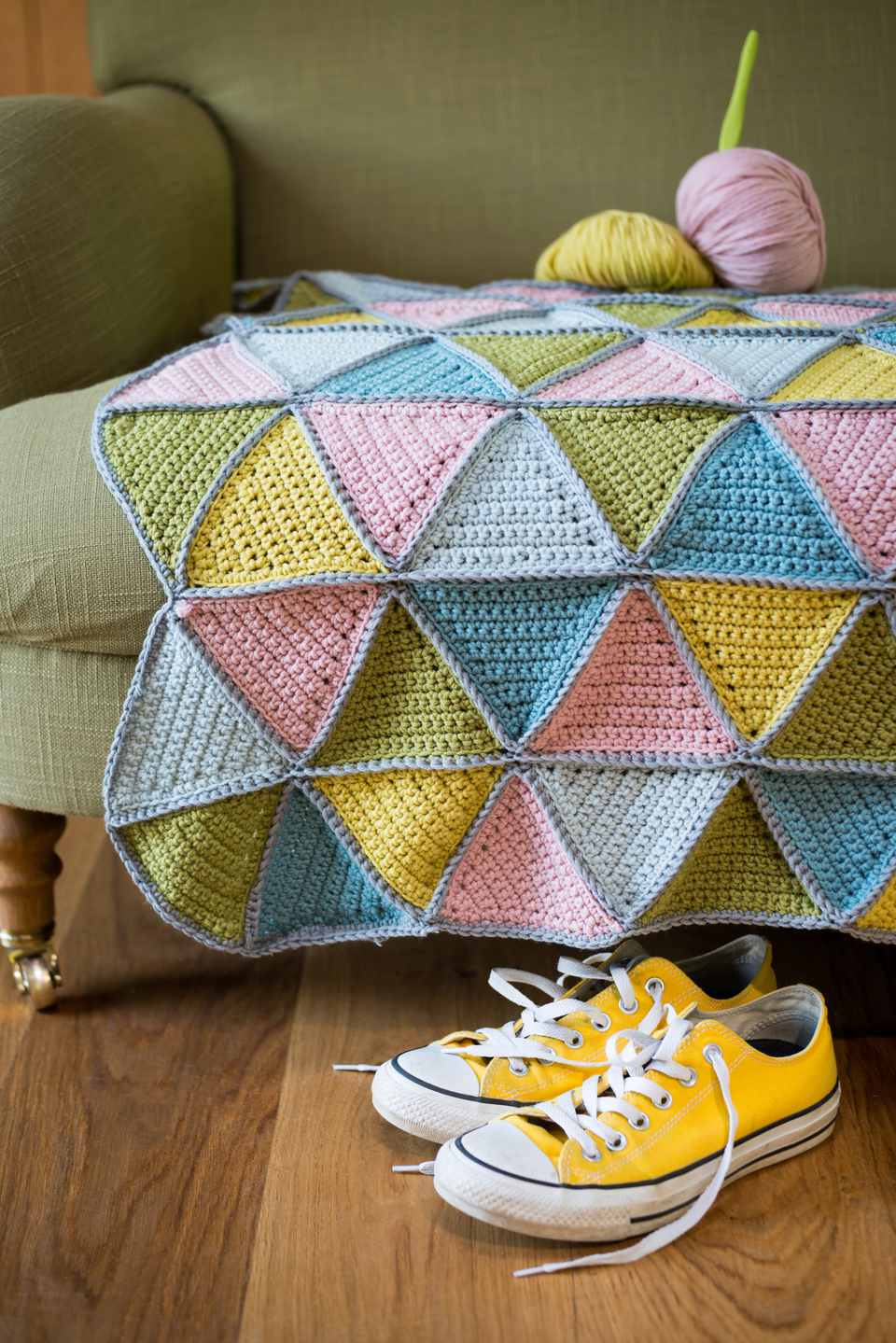 Yellow sneakers under couch with yarn and knitted woolen mat.