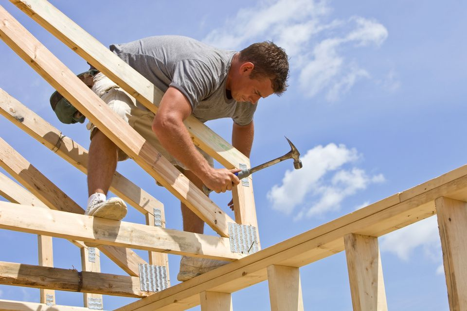 Builder Hammering Roof Truss Nail Against Blue Sky