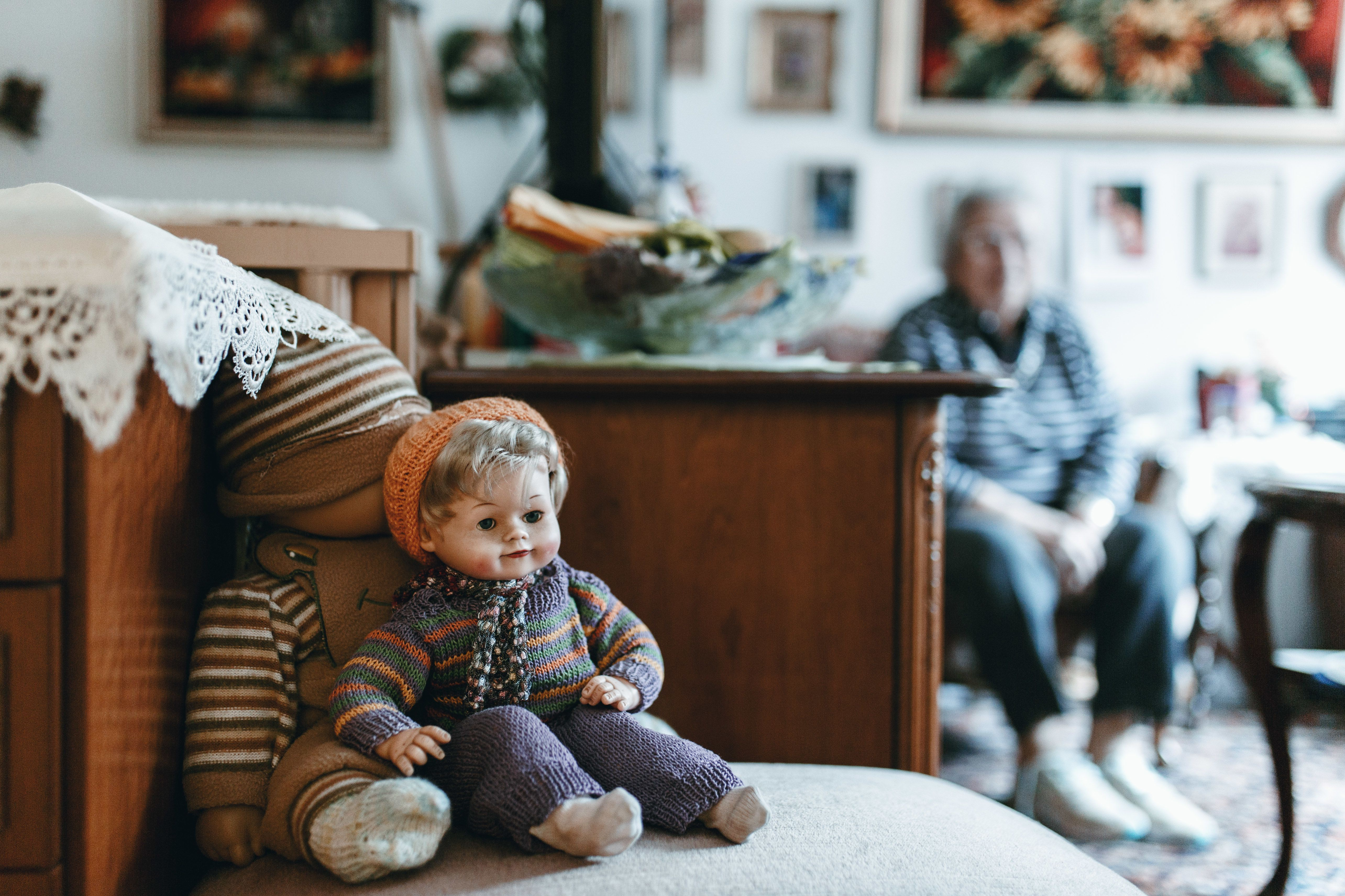 Toys On Seat With Person Sitting In Background At Home