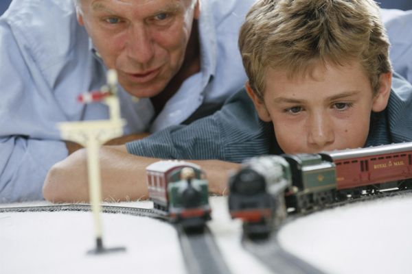 A father and son operating toy trains