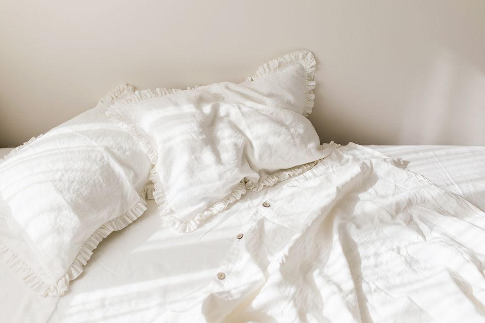 Empty white linen bedding set with ruffle pillows in morning shining sunlight.
