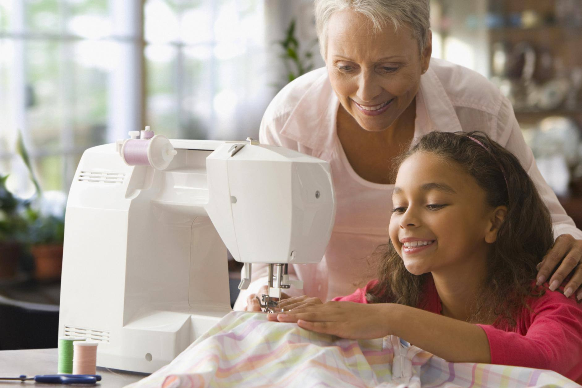 Grandmother teaching granddaughter how to sew