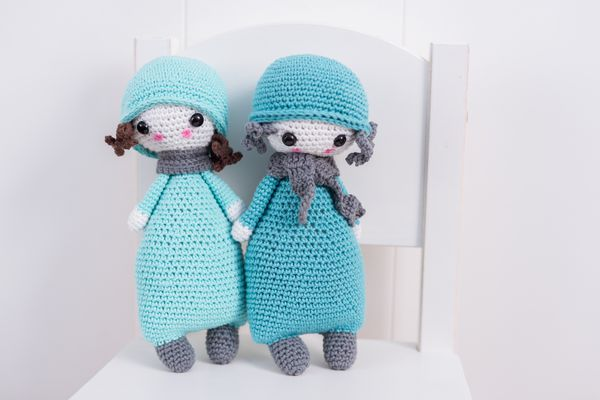 Two handmade crocheted dolls in blue with scarf and hat on a white chair