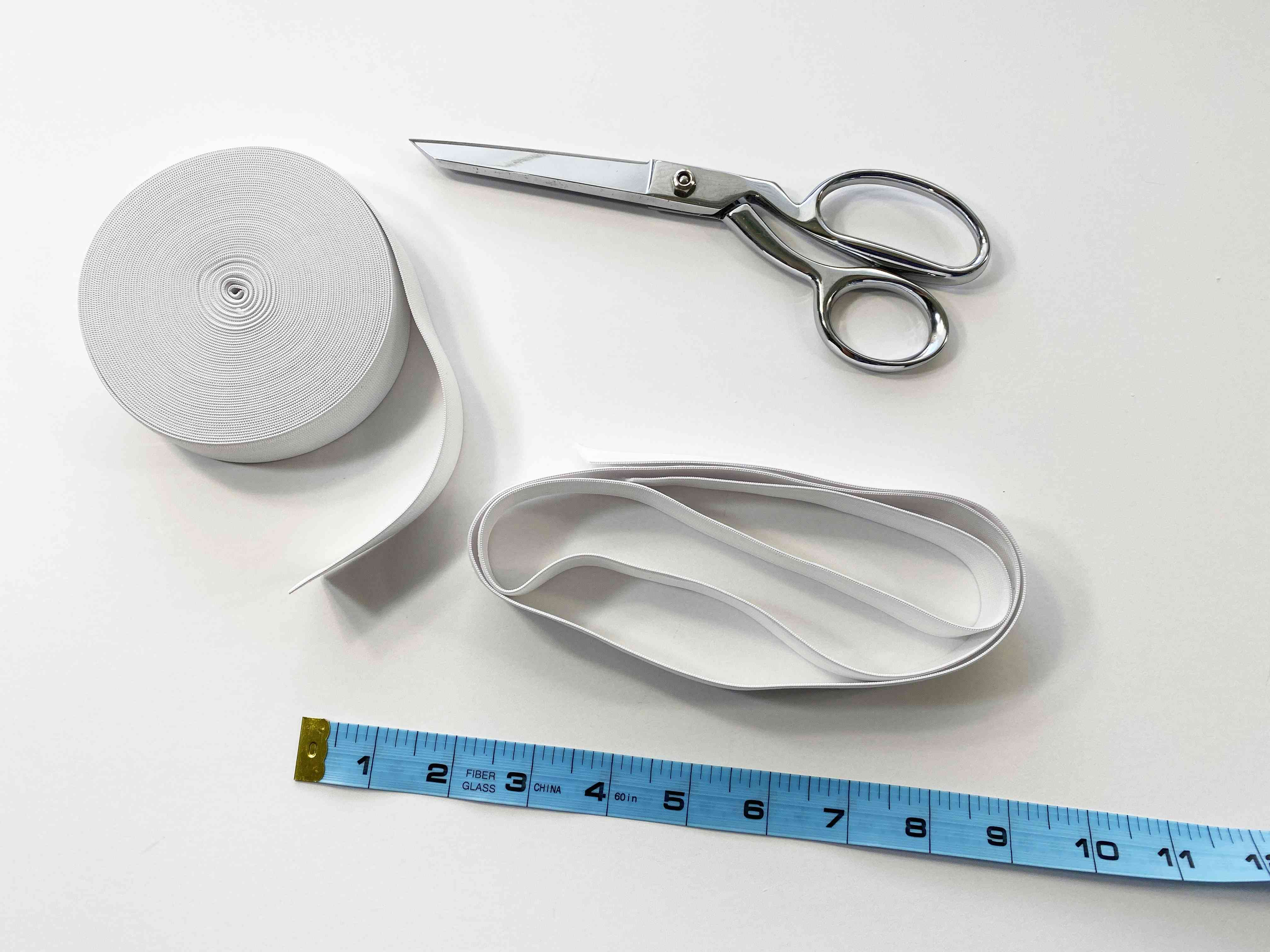 Scissors, elastic, and a measuring tape on a table