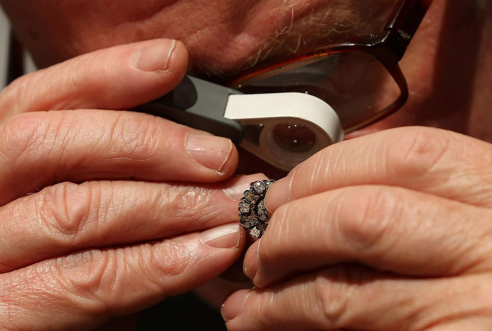 A specialist inspects a pair of antique Russian earrings ahead of the Olympia