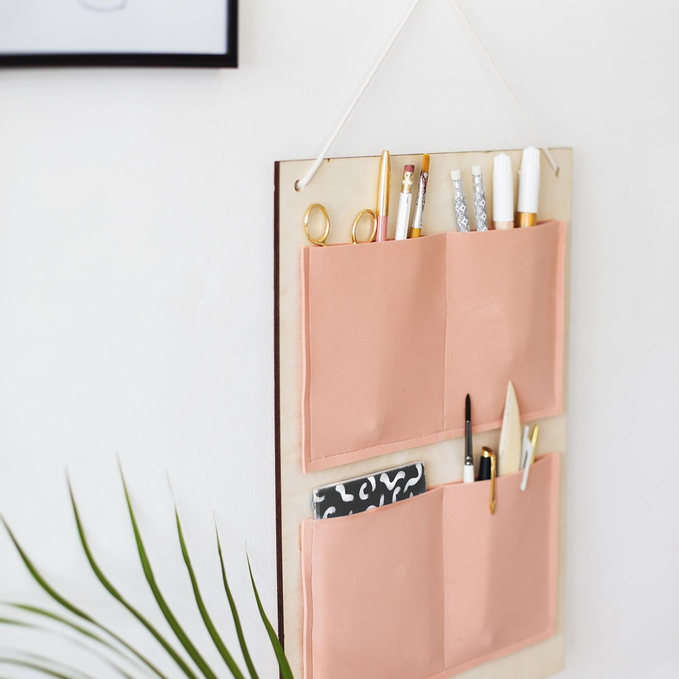 Modern wall organizer with peach colored pockets hanging by art and a plant