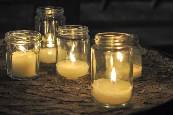 Lit Candles In Mason Jars On Table