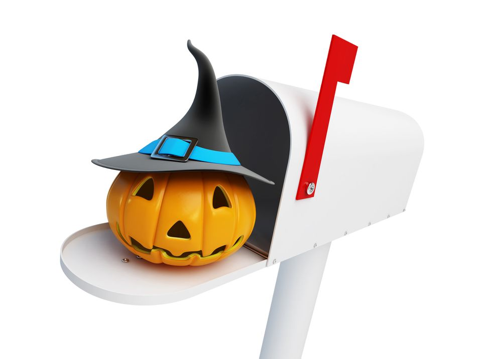 A jack-o-lantern wearing a witch's hat in a white mailbox
