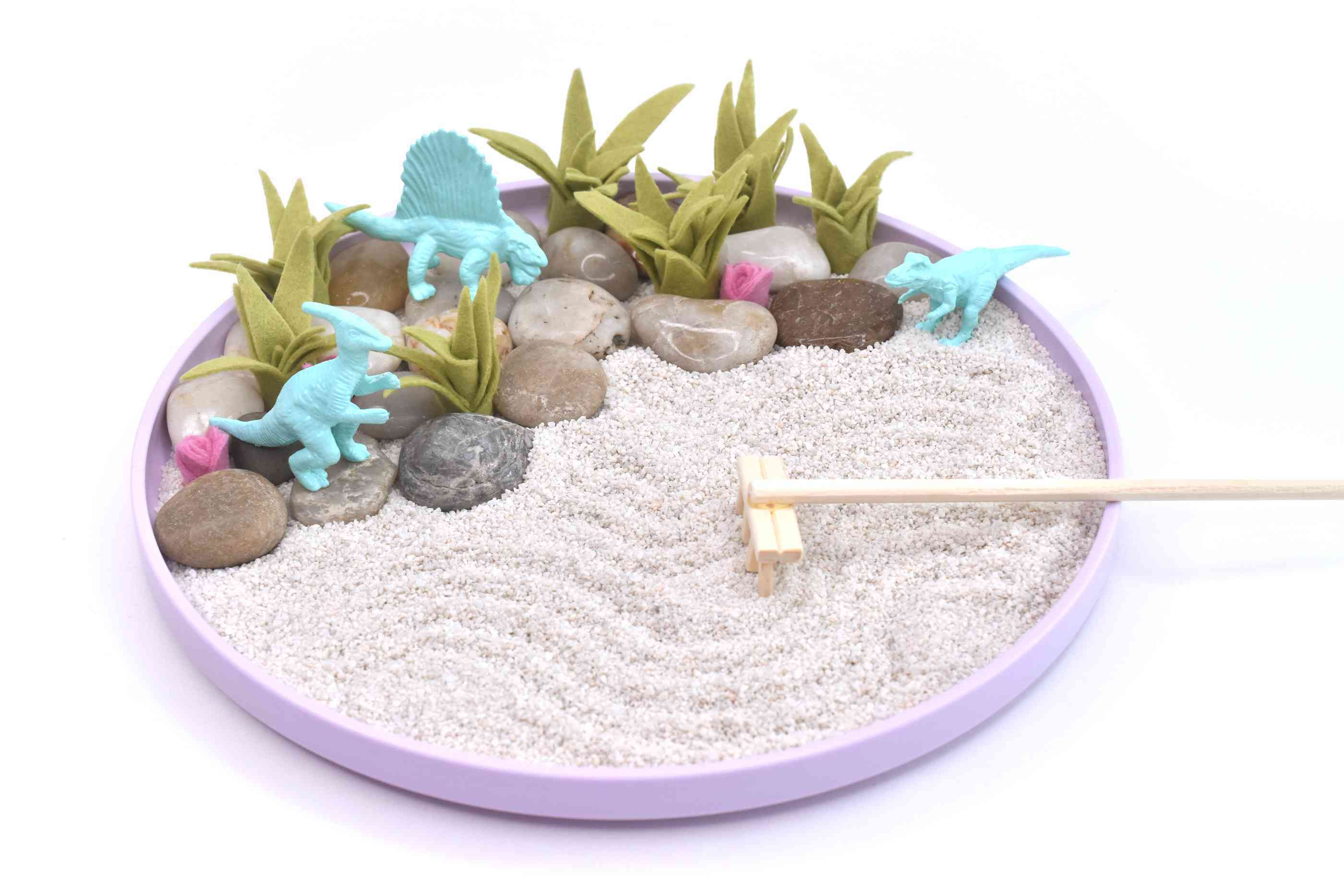 a mindfulness sand garden made with rocks and dinosaur toys