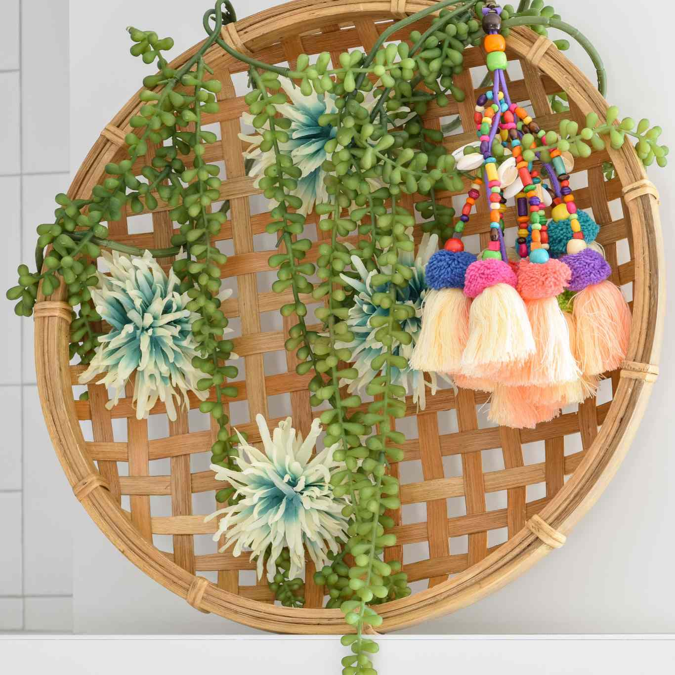 a woven basket with plants and tassels in a wreath