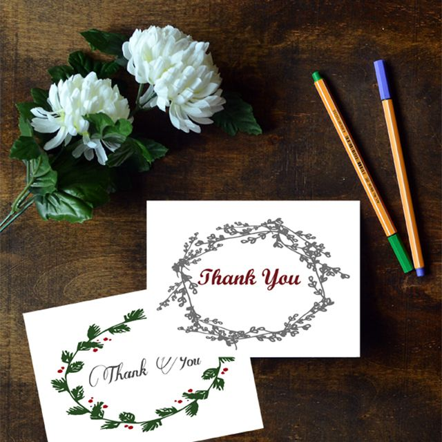 Two Christmas thank you cards laying on a table