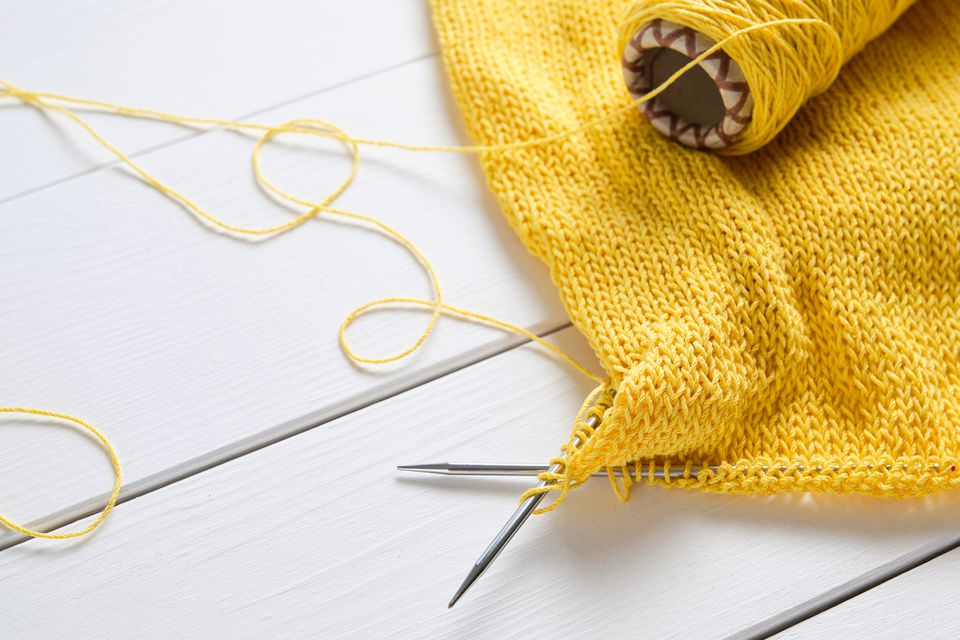An unbound light summer Sweater or cardigan made of cotton. Next to it Lies a Skein of Yarn And Knitting Needles, against the background of a white wooden table. Freelance creative concept of work and life, Hobbies.