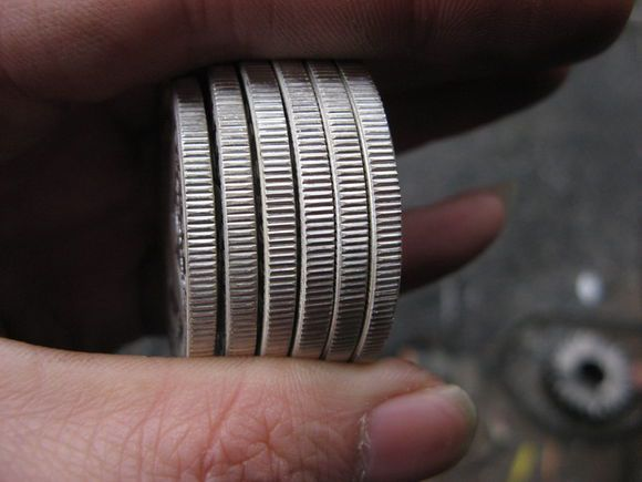 The edges of six fake Morgan silver dollars in someone's hand.