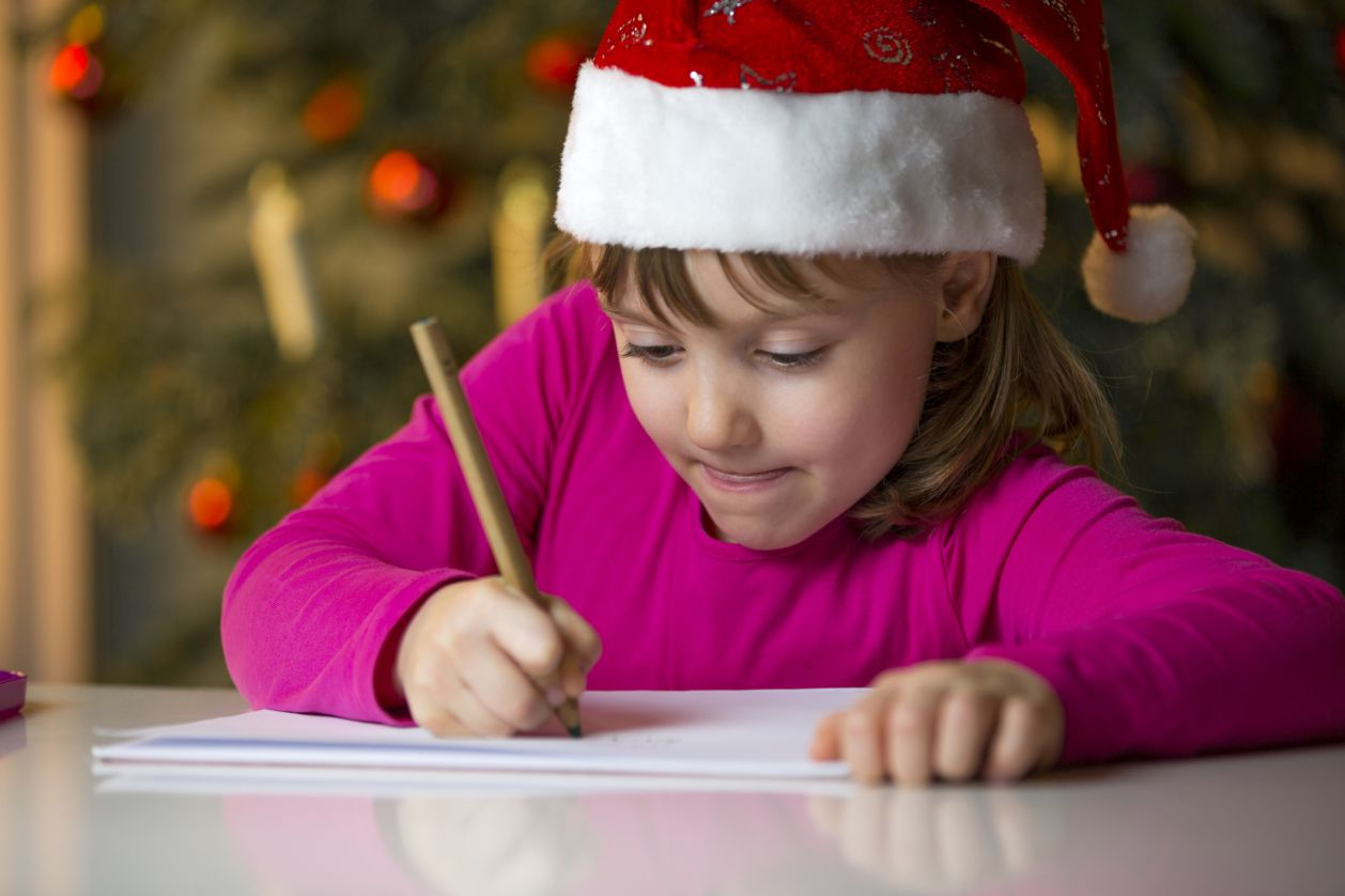 A young girl writing while wearing a Santa hat.