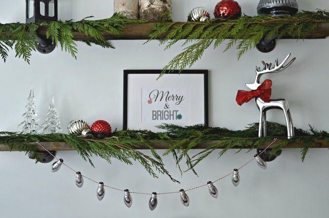 A Christmas banner made of light bulbs on a festively decorated shelf.