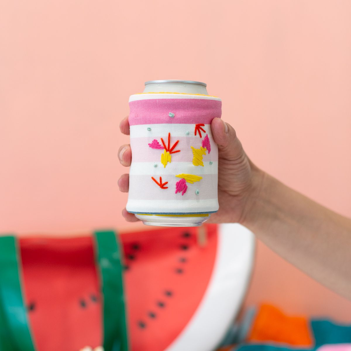 Hand holding a DIY embroidered koozie