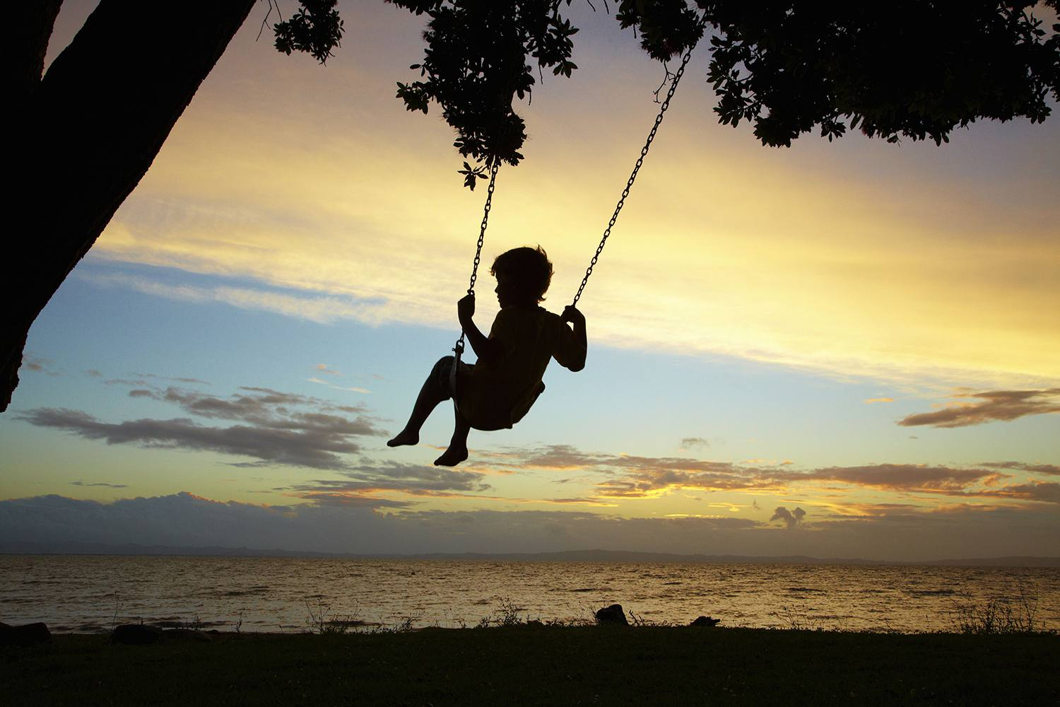 Silhouette of Child on Swing at Sunset