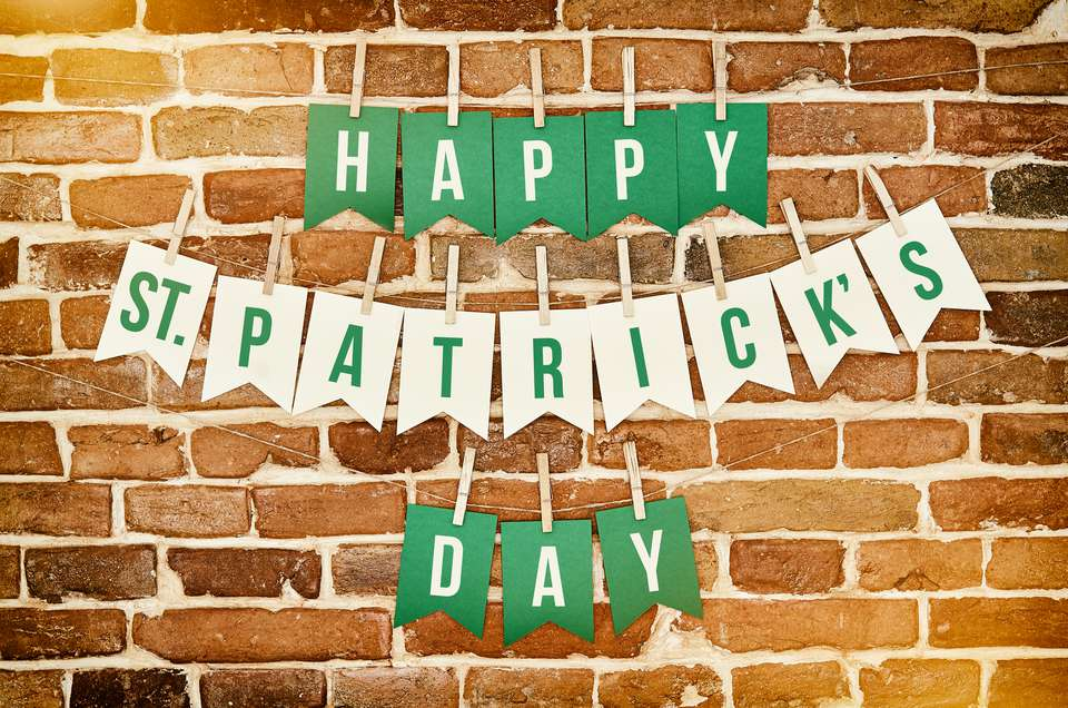Happy St. Patrick's Day banner lettering on brick wall.