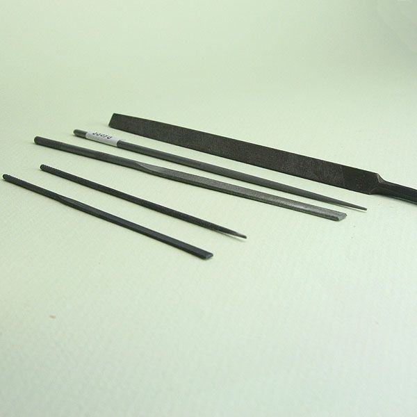 Assortment of miniature metal and wood files for craft work.