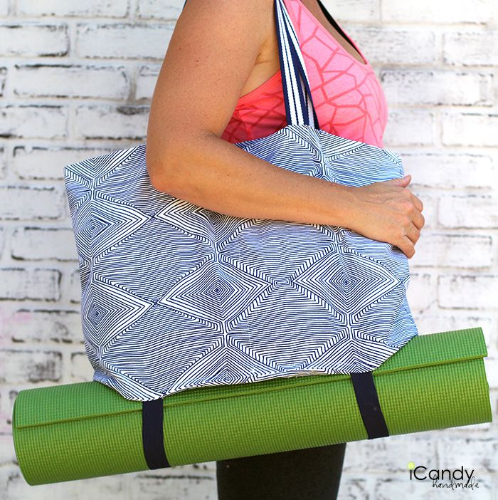 A woman carrying a yoga tote and mat